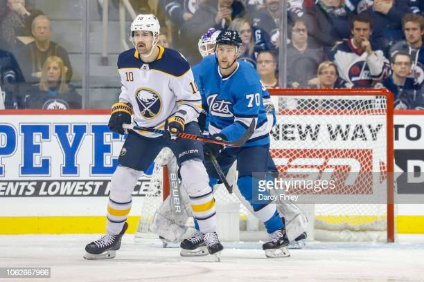 Patrik Berglund of the Buffalo Sabres and Joe Morrow of the Winnipeg Jets keep an eye on the play during first period action at the Bell MTS Place on...