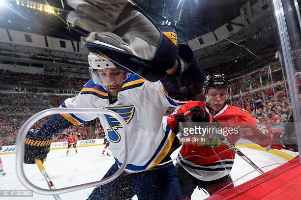 Patrik Berglund of the St Louis Blues and Gustav Forsling of the Chicago Blackhawks chase after the puck by the boards during the season opener at...