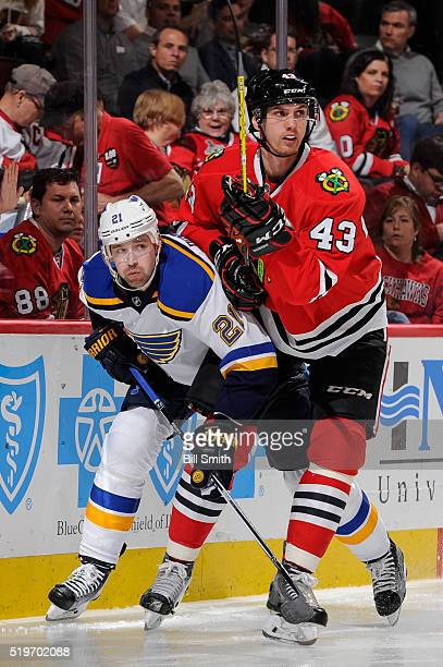 Patrik Berglund of the St Louis Blues and Viktor Svedberg of the Chicago Blackhawks skate around the boards in the third period of the NHL game at...
