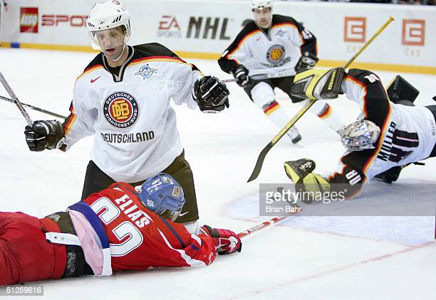 Patrik Elias of the Czech Republic and from the New Jersey Devils ends up sprawled on the ice for a penalty on Robert Leask of Germany while goalie...