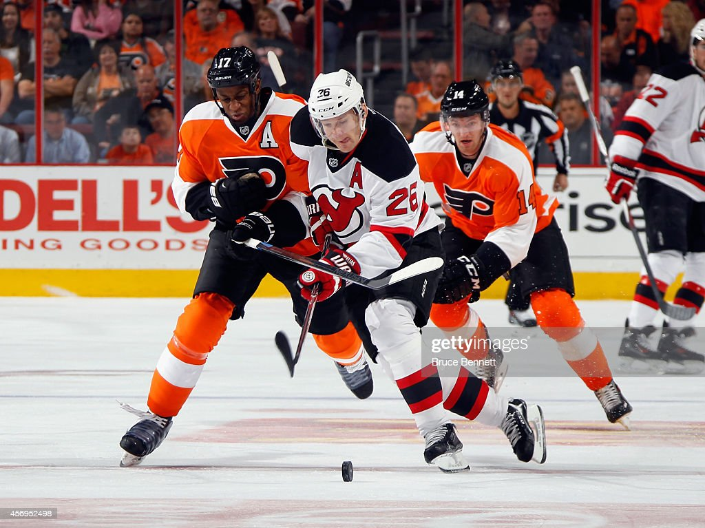 Patrik Elias #26 of the New Jersey Devils carries the puck against Wayne Simmonds #17 of the Philadelphia Flyers during the first period at the Wells Fargo Center on October 9, 2014 in Philadelphia, Pennsylvania.