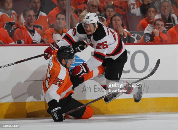 Patrik Elias of the New Jersey Devils flies over Matt Carle of the Philadelphia Flyers during the first period in Game Two of the Eastern Conference...