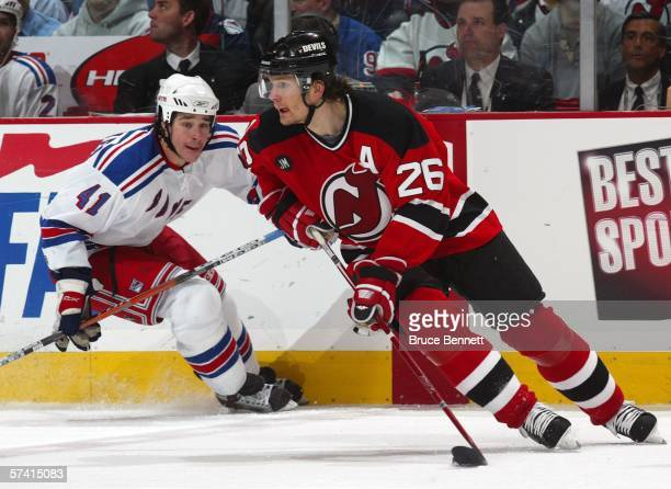 Patrik Elias of the New Jersey Devils handles the puck as Jed Ortmeyer of the New York Rangers gives chase during NHL playoff action at the...