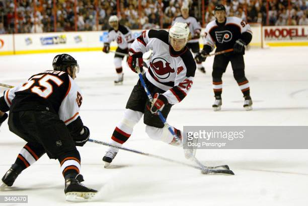 Patrik Elias of the New Jersey Devils takes a shot on goal as Danny Markov of the Philadelphia Flyers defends during game five of the quarterfinals...