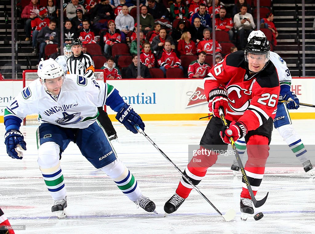 Patrik Elias #26 of the New Jersey Devils takes the puck as Radim Vrbata #17 of the Vancouver Canucks defends in the second period on February 20, 2015 at the Prudential Center in Newark, New Jersey.