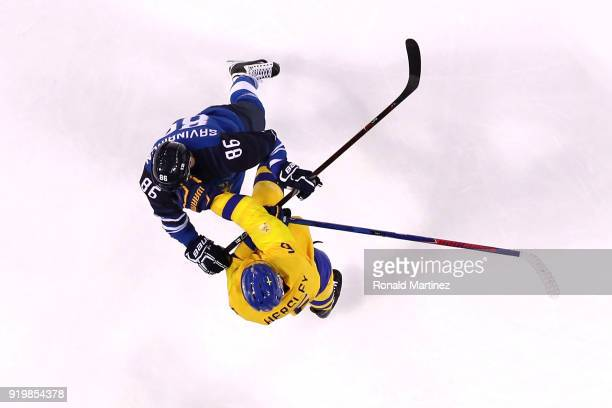 Patrik Hersley of Sweden and Veli-Matti Savinainen of Finland get tangled up in the first period during the Men's Ice Hockey Preliminary Round Group...
