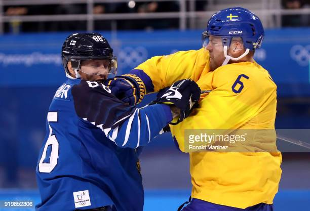 Patrik Hersley of Sweden throws a punch against VeliMatti Savinainen of Finland in the first period during the Men's Ice Hockey Preliminary Round...