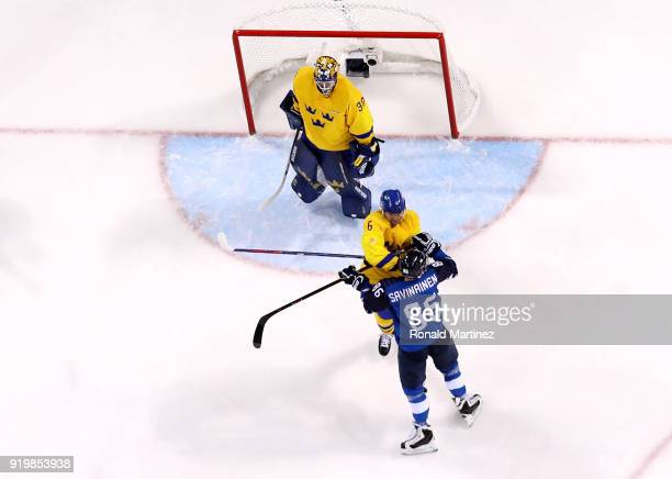 Patrik Hersley of Sweden throws a punch against Veli-Matti Savinainen of Finland in the first period during the Men's Ice Hockey Preliminary Round...