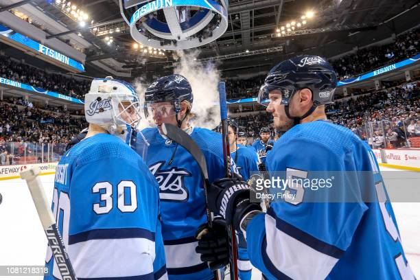 Patrik Laine and Dmitry Kulikov of the Winnipeg Jets congratulate goaltender Laurent Brossoit following a 42 victory over the Detroit Red Wings at...
