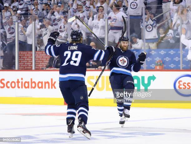 Patrik Laine and Joe Morrow of the Winnipeg Jets celebrate a third period goal against the Minnesota Wild in Game One of the Western Conference First...