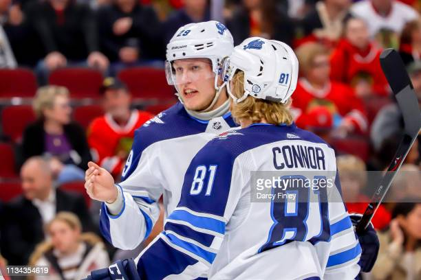 Patrik Laine and Kyle Connor of the Winnipeg Jets discuss strategy during a first period stoppage in play against the Chicago Blackhawks at the...