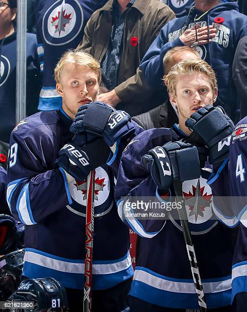 Patrik Laine and Kyle Connor of the Winnipeg Jets look on from the bench during the singing of the National anthems prior to puck drop against the...