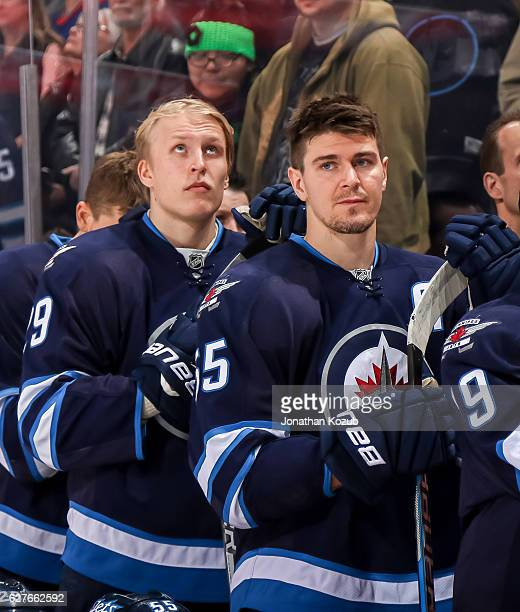 Patrik Laine and Mark Scheifele of the Winnipeg Jets look on from the bench prior to puck drop against the Nashville Predators at the MTS Centre on...
