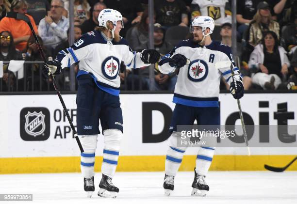 Patrik Laine is congratulated by his teammate Mark Scheifele of the Winnipeg Jets after scoring a secondperiod goal against the Vegas Golden Knights...