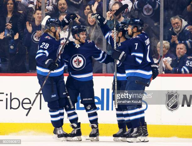 Patrik Laine Nikolaj Ehlers Paul Stastny and Ben Chiarot of the Winnipeg Jets celebrate a first period goal against the Chicago Blackhawks at the...