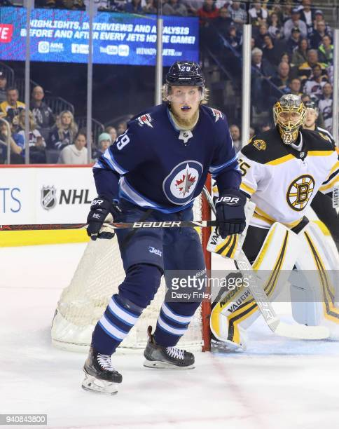 Patrik Laine of the Winnipeg Jets and goaltender Anton Khudobin of the Boston Bruins keep an eye on the play during first period action at the Bell...