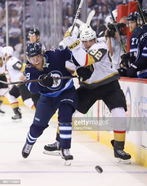 Patrik Laine of the Winnipeg Jets and Tomas Nosek of the Vegas Golden Knights battle along the boards as they chase the puck down the ice during...