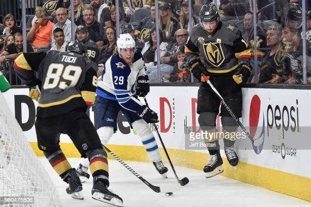 Patrik Laine of the Winnipeg Jets battles for the puck with James Neal and Alex Tuch of the Vegas Golden Knights in Game Four of the Western...