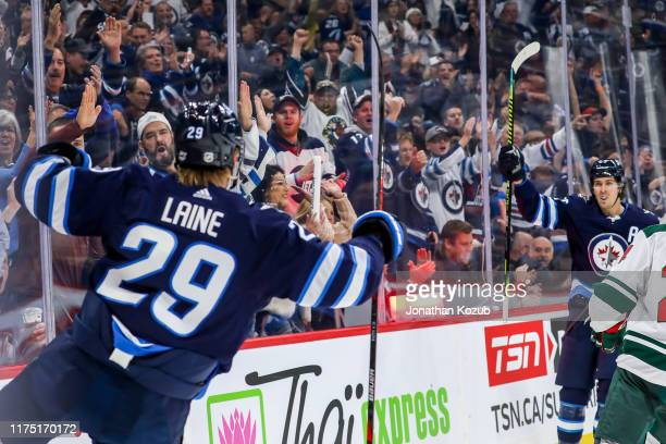 Patrik Laine of the Winnipeg Jets celebrates his second period goal against the Minnesota Wild with teammate Mark Scheifele at the Bell MTS Place on...