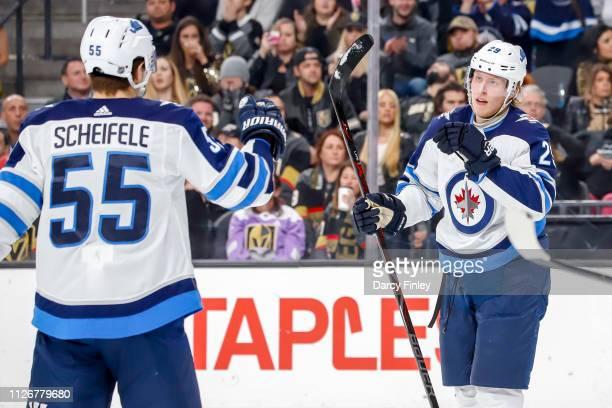 Patrik Laine of the Winnipeg Jets celebrates his third period goal against the Vegas Golden Knights with teammate Mark Scheifele at TMobile Arena on...