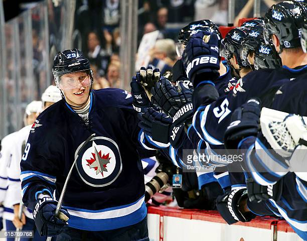 Patrik Laine of the Winnipeg Jets celebrates his third period goal against the Toronto Maple Leafs with teammates at the bench at the MTS Centre on...