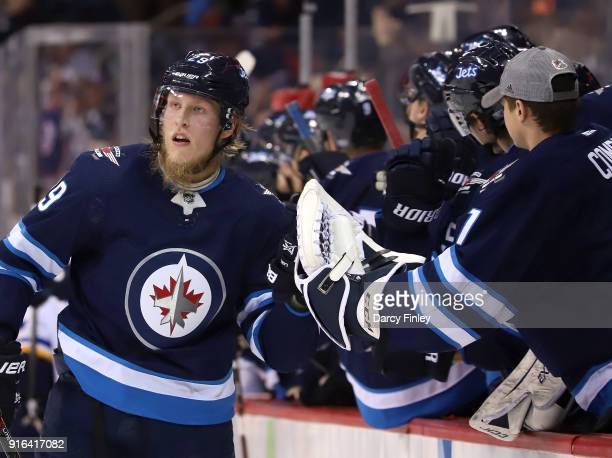 Patrik Laine of the Winnipeg Jets celebrates his third period goal against the St Louis Blues with teammates at the bench at the Bell MTS Place on...