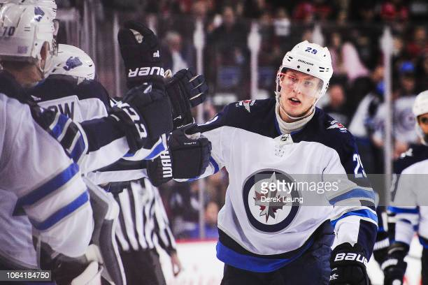 Patrik Laine of the Winnipeg Jets celebrates with the bench after scoring against the Calgary Flames during an NHL game at Scotiabank Saddledome on...