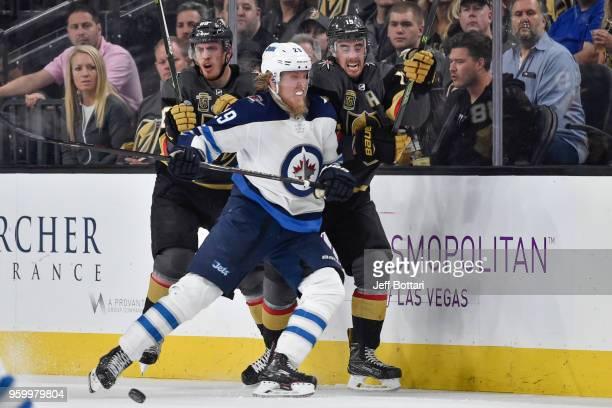 Patrik Laine of the Winnipeg Jets collides with Reilly Smith and Nate Schmidt of the Vegas Golden Knights in Game Four of the Western Conference...
