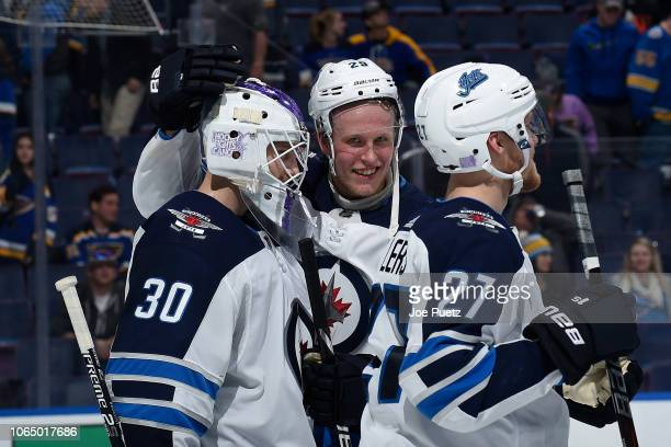 Patrik Laine of the Winnipeg Jets congratulates Laurent Brossoit of the Winnipeg Jets after beating the St Louis Blues 84 at Enterprise Center on...