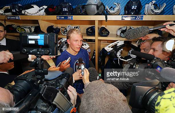 Patrik Laine of the Winnipeg Jets faces a throng of media following a 54 overtime victory over the Carolina Hurricanes in his NHL debut at the MTS...