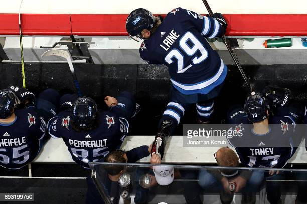 Patrik Laine of the Winnipeg Jets gets an adjustment on his skates at the bench during second period action against the Chicago Blackhawks at the...