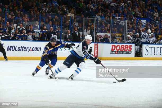 Patrik Laine of the Winnipeg Jets handles the puck against Robby Fabbri of the St Louis Blues at the Scottrade Center on January 31 2017 in St Louis...