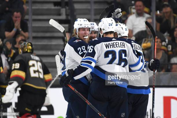 Patrik Laine of the Winnipeg Jets is congratulated by his teammates after scoring a second-period goal as Marc-Andre Fleury of the Vegas Golden...