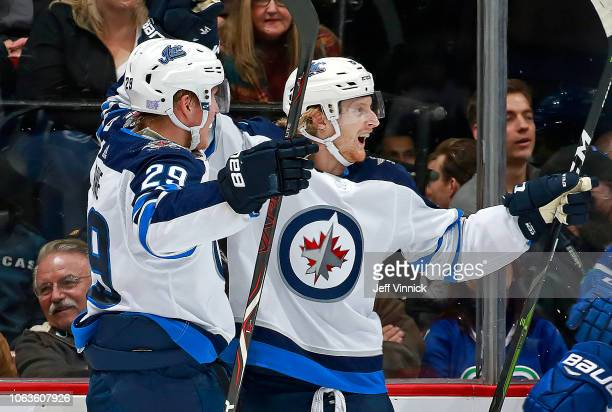 Patrik Laine of the Winnipeg Jets is congratulated by teammates after scoring during their NHL game against the Vancouver Canucks at Rogers Arena...