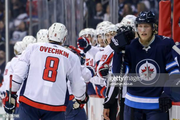 Patrik Laine of the Winnipeg Jets looks on as Alex Ovechkin of the Washington Capitals celebrates a first period goal with teammates at the bench at...