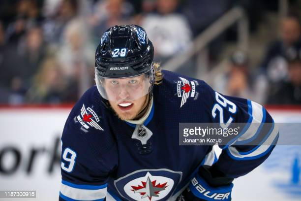 Patrik Laine of the Winnipeg Jets looks on as he gets set for a third period face-off against the Vancouver Canucks at the Bell MTS Place on November...