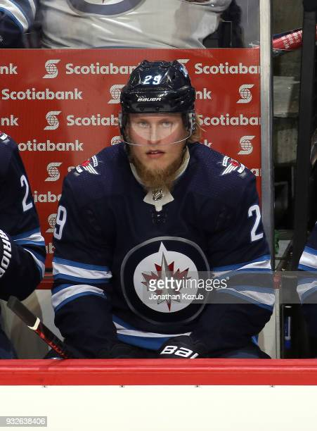Patrik Laine of the Winnipeg Jets looks on from the bench during third period action against the Chicago Blackhawks at the Bell MTS Place on March 15...
