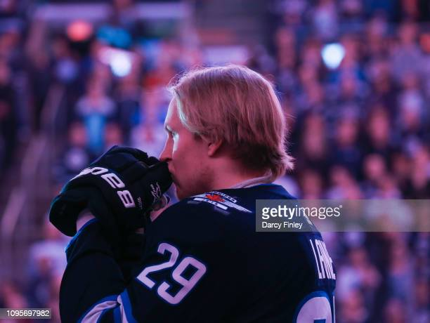 Patrik Laine of the Winnipeg Jets looks on from the bench during the singing of the National anthems prior to puck drop against the Anaheim Ducks at...
