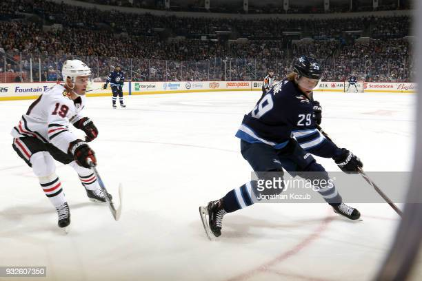 Patrik Laine of the Winnipeg Jets plays the puck along the boards as Jonathan Toews of the Chicago Blackhawks defends during second period action at...