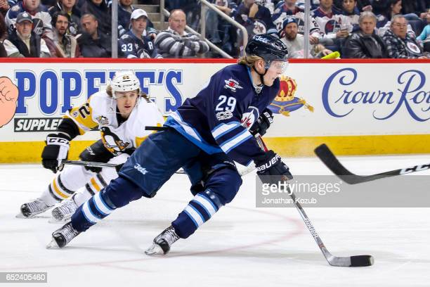 Patrik Laine of the Winnipeg Jets plays the puck as Carl Hagelin of the Pittsburgh Penguins gives chase during third period action at the MTS Centre...