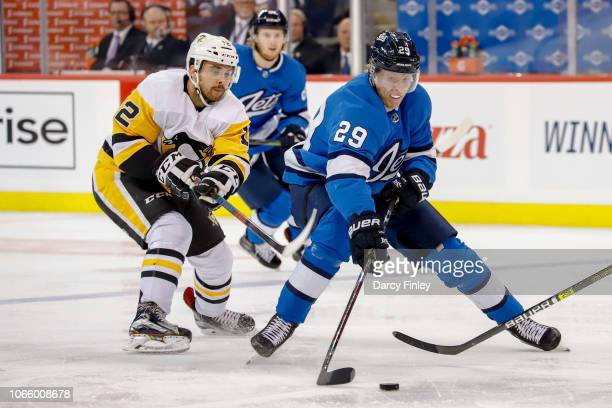 Patrik Laine of the Winnipeg Jets plays the puck down the ice as Dominik Simon of the Pittsburgh Penguins gives chase during third period action at...