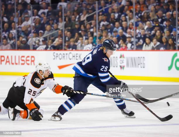 Patrik Laine of the Winnipeg Jets plays the puck down the ice as Ondrej Kase of the Anaheim Ducks falls to the ice while giving chase during third...