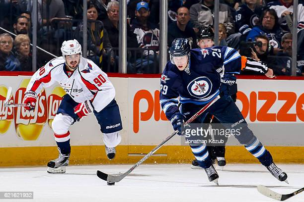 Patrik Laine of the Winnipeg Jets plays the puck down the ice as Marcus Johansson of the Washington Capitals gives chase during second period action...
