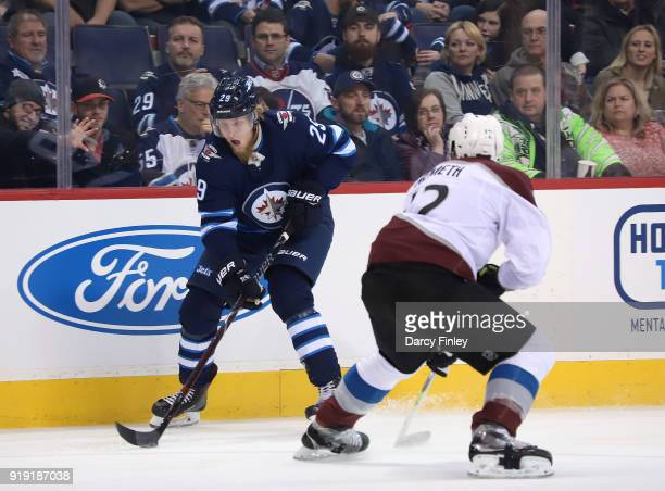 Patrik Laine of the Winnipeg Jets plays the puck down the ice as Patrik Nemeth of the Colorado Avalanche defends during first period action at the...
