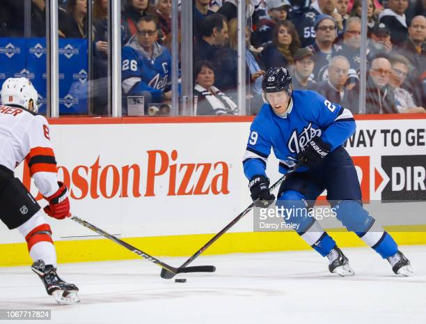Patrik Laine of the Winnipeg Jets plays the puck down the ice as Will Butcher of the New Jersey Devils defends during second period action at the...