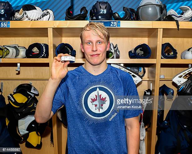 Patrik Laine of the Winnipeg Jets poses with the game puck after scoring his first career NHL goal in a 54 overtime victory over the Carolina...