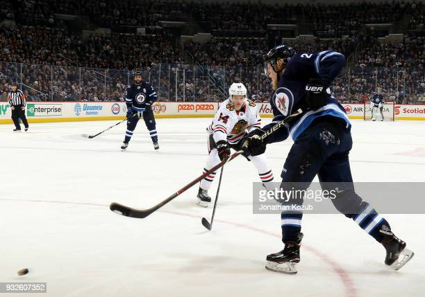 Patrik Laine of the Winnipeg Jets shoots the puck past a defending David Kampf of the Chicago Blackhawks during second period action at the Bell MTS...