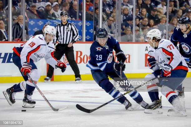 Patrik Laine of the Winnipeg Jets skates between Nicklas Backstrom and TJ Oshie of the Washington Capitals as they watch the loose puck during second...