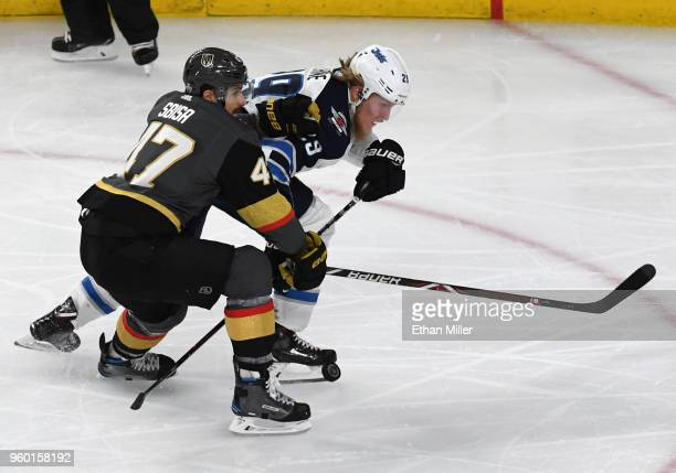 Patrik Laine of the Winnipeg Jets skates with the puck against Luca Sbisa of the Vegas Golden Knights in the first period of Game Four of the Western...
