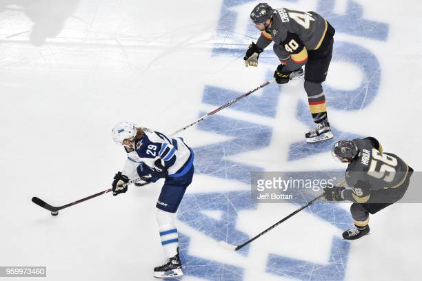 Patrik Laine of the Winnipeg Jets skates with the puck while Ryan Carpenter and Erik Haula of the Vegas Golden Knights defend in Game Four of the...